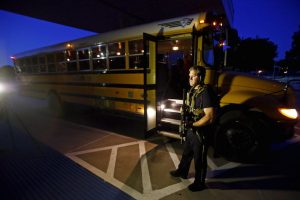 A police officer stands near a school bus used to evacuate attendees of the Muhammad Art Exhibit and Contest sponsored by the American Freedom Defense Initiative after a shooting outside the Curtis Culwell Center where the event was held in Garland, Texas.