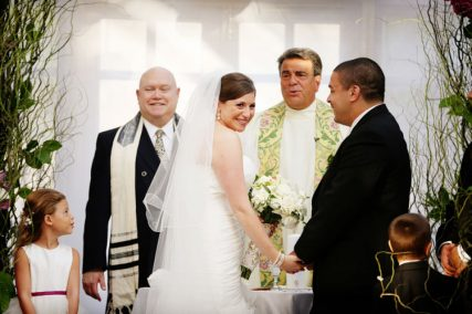 Rachel and Rich Mejias wed at the Brownstone in Patterson, New Jersey, with priest and rabbi officiants.