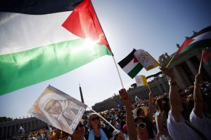Members of the faithful wave Palestinian flags before Pope Francis leads a ceremony for the canonization of two Palestininan nuns, Marie Alphonsine Ghattas, founder of the first Catholic congregation in Palestine, and Mariam Baouardy Haddad, who established a Carmelite convent in Bethlehem.