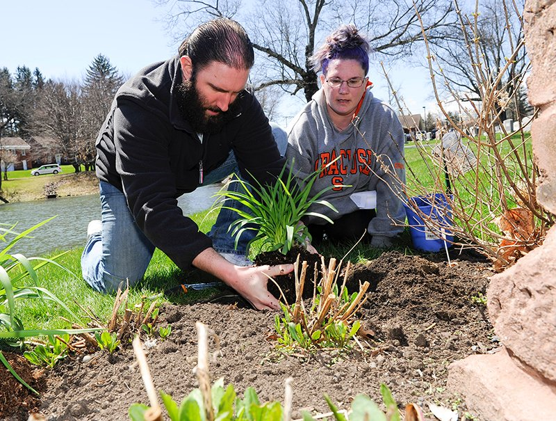 Christopher Sifaa and his wife Jennifer Sifaa of Albany, N.Y., plant Stella D'Oro daylilly in memory of their child during a memorial service for mothers who lost their children before birth at the Most Holy Redeemer cemetery in Niskayuna, N.Y., on Tuesday, April 28, 2015. Photo by Hans Pennink / Special to Religion News Service