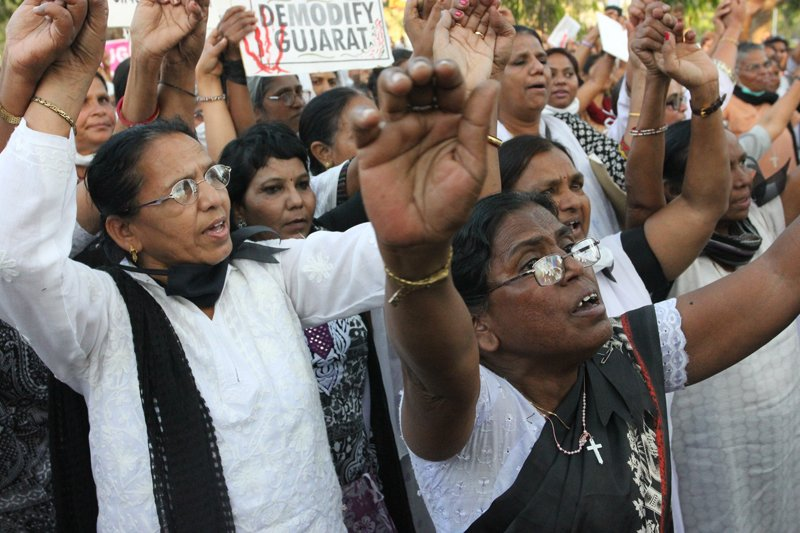 Women raise their hands and voices during a rally held in Ahmedabad, Gujurat, after a nun was raped in Kolkata, West Bengal. Religion News Service photo by Arielle Dreher