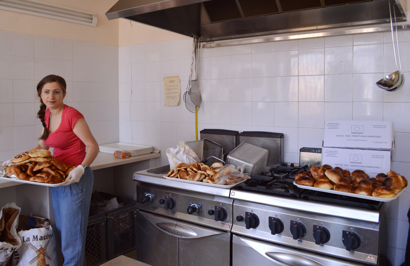 Graziana Pistorio, a volunteer, prepares food donated by local bakeries at the Caritas center in Catania, Sicily. Religion News Service photo by Rosie Scammell