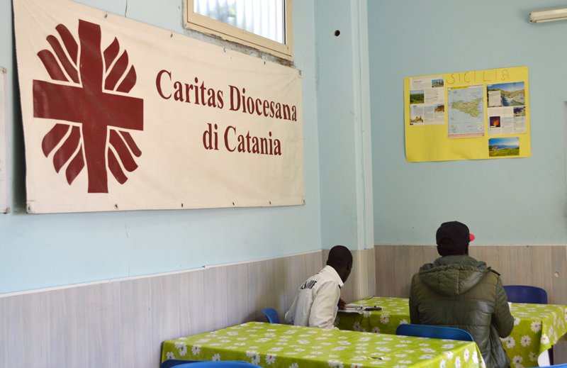Migrants sit at the Caritas center in Catania, Sicily. Religion News Service photo by Rosie Scammell
