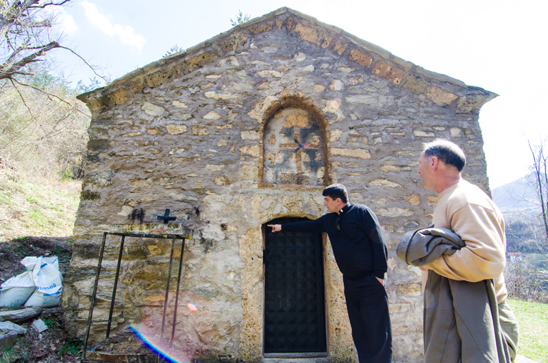 Don Albert Jakaj explains the architecture of St. John Church to the village locals, including the mayor of Brod, right, in Kosovo on April 13, 2015. Jakaj believes the church is a Roman Catholic burial church. Religion News Service photo by Valerie Plesch