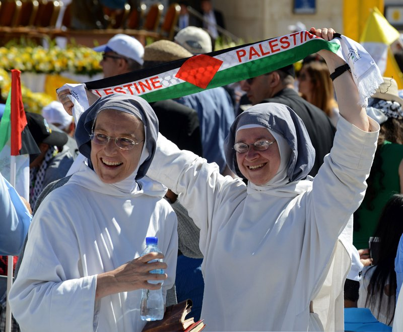 A nun holds up a scarf that reads 'PALESTINE' before Pope Francis celebrates Mass in Manger Square outside the Church of the Nativity in Bethlehem, West Bank, on May 25, 2014. Photo by Debbie Hill, courtesy of Catholic News Service