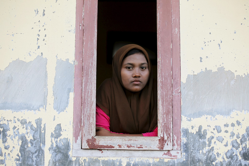 A Rohingya migrant woman, who arrived in Indonesia by boat, looks from a window of a shelter inside a temporary compound for refugees in Kuala Cangkoi village in Lhoksukon, Indonesia's Aceh Province, on May 17, 2015. The United Nations has called on countries around the Andaman Sea not to push back the thousands of desperate Bangladeshis and Rohingya Muslims from Myanmar now stranded in rickety boats, and to rescue them instead. Photo courtesy of  REUTERS/Beawiharta *Editors: This photo may only be republished with RNS-ROHINGYA-SPLAINER, originally transmitted on May 19, 2015.