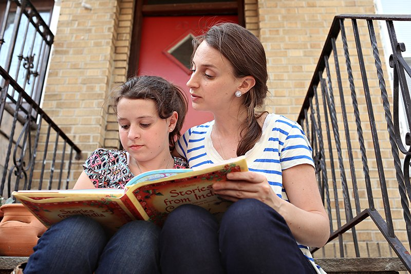 Eliza Lamb and her daughter, Madeline, or Maddy, at their home in the Astoria neighborhood of Queens, New York, on Monday, May 4, 2015. Maddie attends a Catholic school but is learning about other religions through reading about them. Religion News Service photo by Alexander Cohn