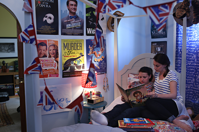 Eliza Lamb and her daughter, Madeline, or Maddy, at their home in the Astoria neighborhood of Queens, New York, Monday, on May 4, 2015. Maddie attends a Catholic school but is learning about other religions through reading about them. They often read together in Maddie's bedroom, seen here. Maddie says that she has seen all the Broadway musicals whose posters are on her walls. Religion News Service photo by Alexander Cohn