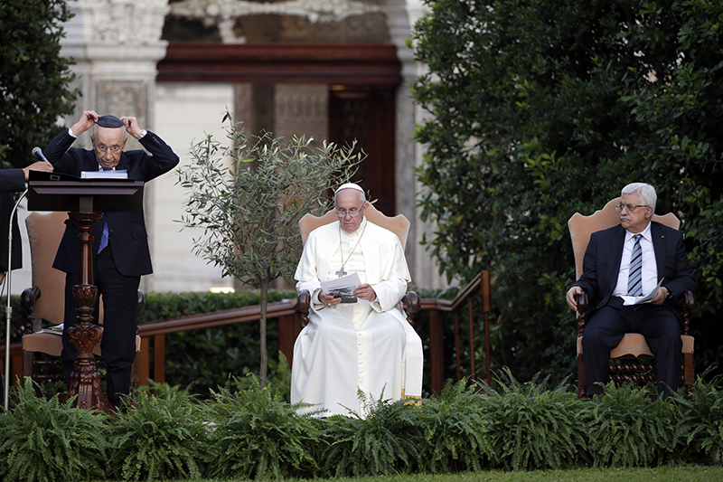 Israeli President Shimon Peres puts on a kippah before speaking next to Pope Francis and Palestinian President Mahmoud Abbas, far right, in the Vatican Gardens at the Vatican on June 8, 2014. Photo courtesy of REUTERS/Max Rossi *Editors: This photo may only be republished with RNS-VATICAN-PALESTINE, originally transmitted on May 13, 2015.