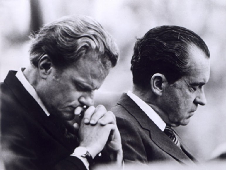 RNS GRAHAM: Knoxville, Tenn. -- President Richard M. Nixon (right) and Billy Graham bow their heads in prayer during the President's visit to the Billy Graham East Tennessee Crusade at Knoxville, Tenn. Religion News Service file photo, 1970