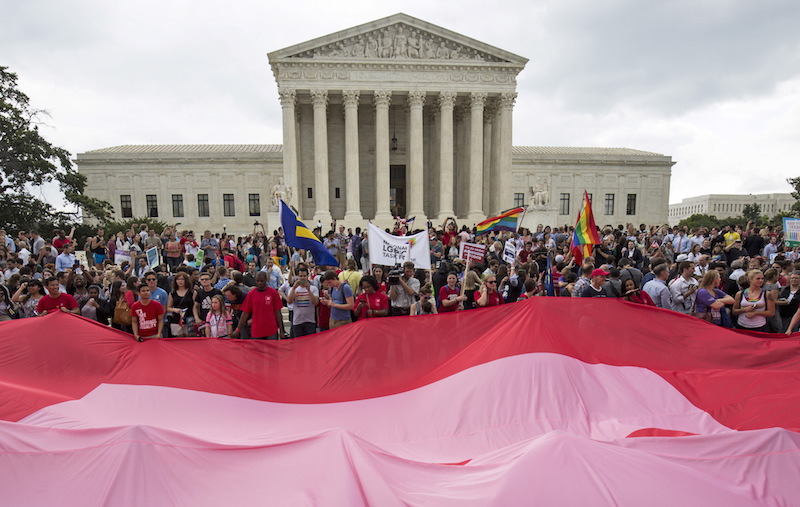 Supporters of gay marriage outside the U.S. Supreme Court building wave a pink and red tarps.