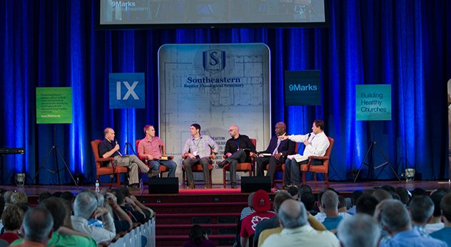 Hundreds of ministers and seminary students attend a IX Marks conference in 2012 at Southeastern Baptist Theological Seminary in Wake Forest, NC. From left: Daniel Akin, President of Southeastern Seminary; David Platt, president of International Mission Board; Matt Chandler, pastor of The Village Church; Jonathan Leeman, editorial director of IX Marks; Thabiti Anyabwile, assistant pastor for church planting at Capitol Hill Baptist Church; Mark Dever, founder of IX Marks. (Image courtesy of Southeastern Baptist Theological Seminary)