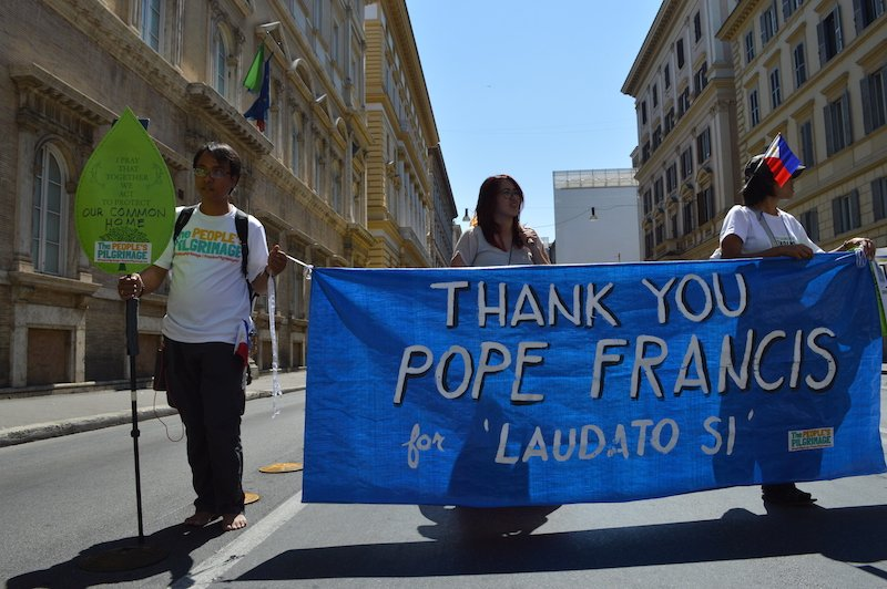 "A group of marchers with a banner saying, ""Thank you Pope Francis."""