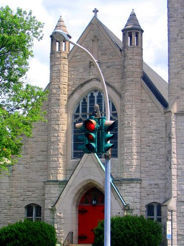 Red stop light in front of a church.