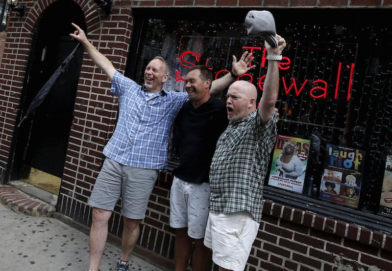 Three men celebrate outside the Stonewall Inn in the Greenwich Village neighborhood of New York, June 26, 2015, following the announcement that the U.S. Supreme Court had ruled that the U.S. Constitution provides same-sex couples the right to marry in a historic triumph for the American gay rights movement.  REUTERS/Mike Segar - RTX1HXY1