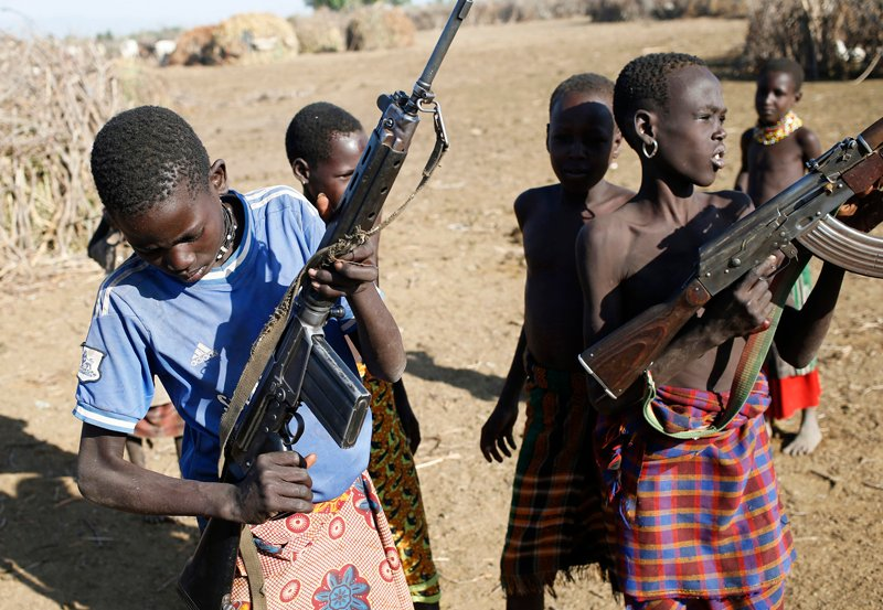 Turkana boys play with rifles in a village inside the Turkana region of the Ilemi Triangle, northwest Kenya on December 21, 2014. Photo courtesy of REUTERS/Goran Tomasevic *Editors: This photo may only be republished with RNS-ALSHABAB-KENYA, originally transmitted on June 22, 2015.