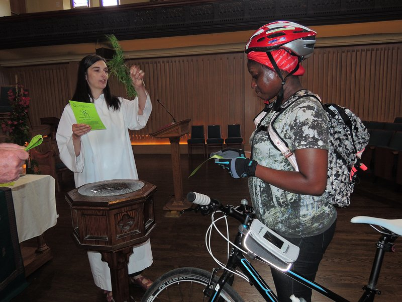 Using a sprig of cedar, officiant Ann Russell sprinkles holy water on a bike and its rider at the sixth annual Blessing of the Bikes at Toronto's Trinity-St. Paul's United Church on June 7, 2015. Religion News Service photo by Ron Csillag