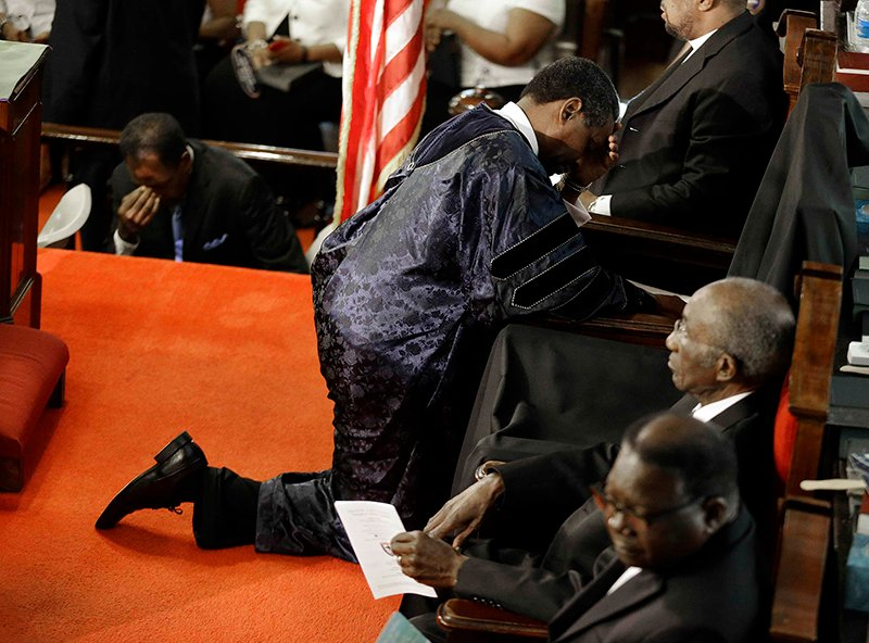 Rev. Norvel Goff prays at the empty seat of the Rev. Clementa Pinckney at Emanuel African Methodist Episcopal Church in Charleston, South Carolina, on June 21, 2015. The church held its first service since a mass shooting left nine people dead during a bible study. Photo courtesy of REUTERS/David Goldman/Pool *Editors: This photo may only be republished with RNS-CHARLESTON-AME, originally transmitted on June 22, 2015.