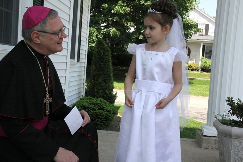 Bishop Thomas J. Tobin of Providence, R.I., greets Sydney Khoury outside the rectory of St. Philip Church in Greenville on May 31, 2011. Photo by Rick Snizek, the Rhode Island Catholic, courtesy of Catholic News Service