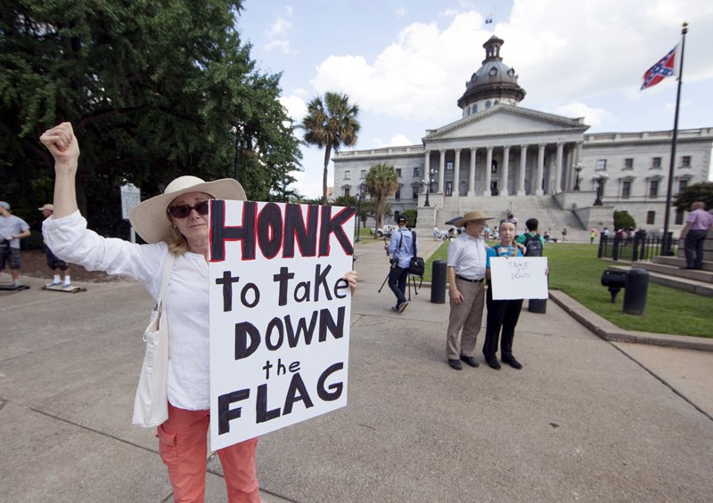 Sheila DiCiorrio holds a sign asking for the Confederate battle flag that flies at the South Carolina State House to be removed in Columbia, S.C., on June 20, 2015. Photo courtesy of REUTERS/Jason Miczek<br /> *Editors: This photo may only be republished with RNS-CONFEDERATE-FLAG, originally transmitted on June 22, 2015.*Editors: This photo may only be republished with RNS-CONFEDERATE-FLAG, originally transmitted on June 22, 2015.
