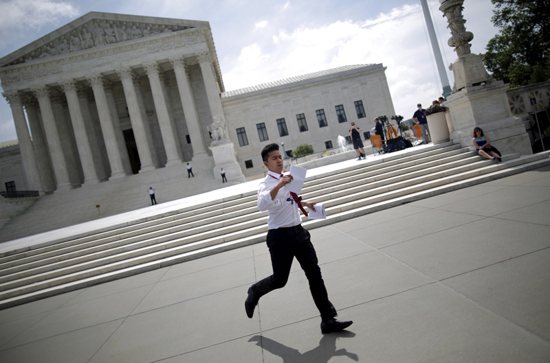 A news assistant runs copies of court rulings to his fellow reporters outside the U.S. Supreme Court in Washington on June 18, 2015. The U.S. Supreme Court ruled that a town in Arizona violated a local church's free speech rights by preventing it from posting signs notifying the public of its worship services. The court, on a unanimous 9-0 vote, ruled in favor of Good News Community Church, which objected to its treatment by town officials in Gilbert, Arizona. Photo courtesy of REUTERS/Carlos Barria *Editors: This photo may only be republished with RNS-COURT-SIGNS, originally transmitted on June 18, 2015.