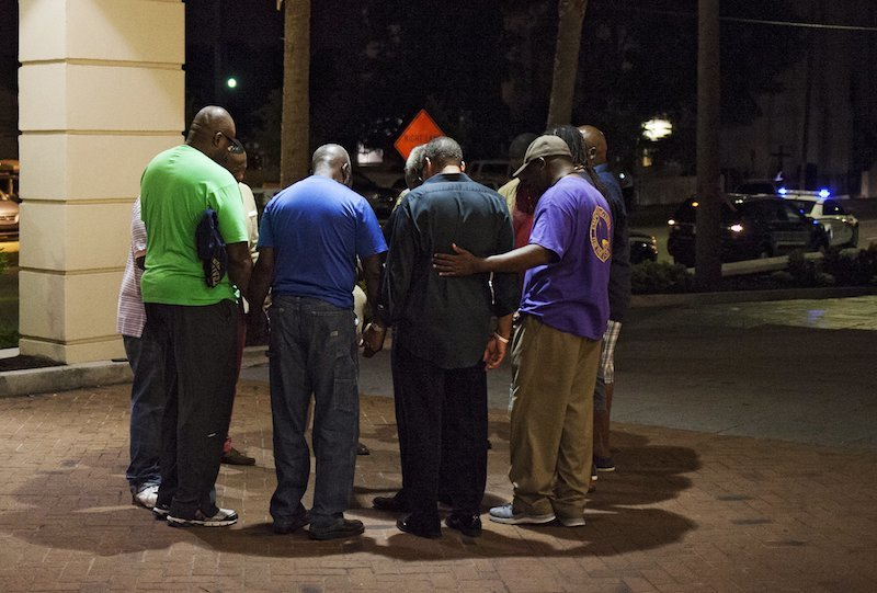 A small prayer circle forms nearby where police are responding to a shooting at the Emanuel AME Church in Charleston, South Carolina, June 17, 2015. A gunman opened fire on Wednesday evening at the historic African-American church in downtown Charleston. REUTERS/Randall Hill