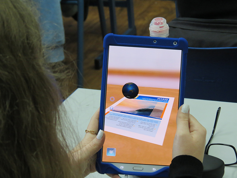 A student tinkers with augmented reality technology on her tablet, pointing the camera over the printed textbook and watching the pages come to life. Photo courtesy of Museum of the Bible