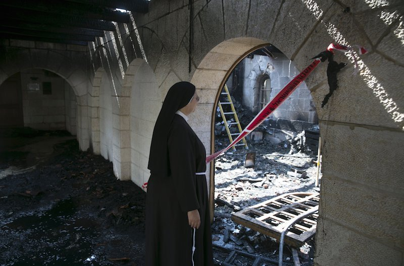 A nun looks at damage caused by a fire in the Church of Loaves and Fishes on the shores of the Sea of Galilee in northern Israel June 18, 2015. Photo by Baz Ratner courtesy of Reuters