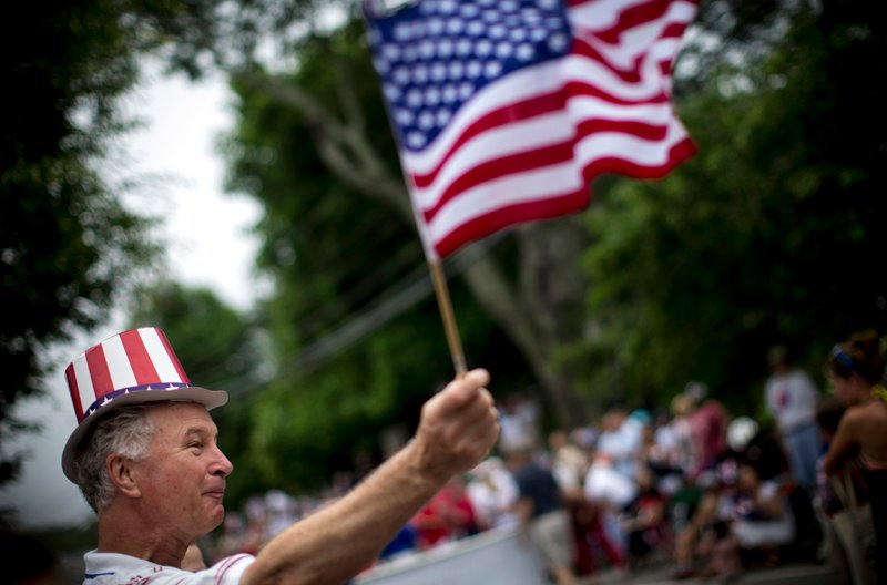 A man waves an American flag as he watches a July Fourth parade in the village of Barnstable, Massachusetts on July 4, 2014. Photo couretsy of REUTERS/Mike Segar *Editors: This photo may only be republished with RNS-PATRIOTIC-SURVEY, originally transmitted on June 23, 2015.
