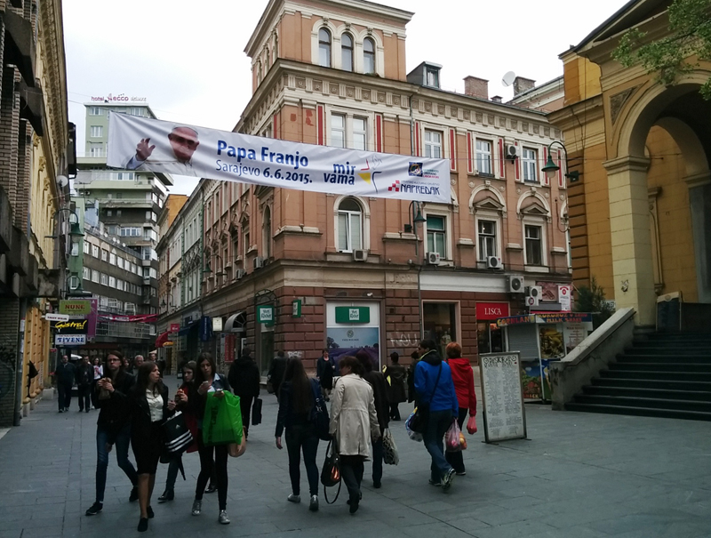 A banner advertising the Pope's visit to Bosnia hangs in Sarajevo as people pass below. Religion News Service photo by Brian Pellot
