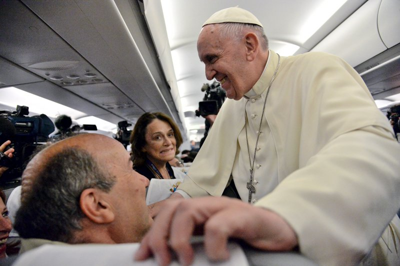Pope Francis greets journalists on his flight back from Sarajevo to Rome on June 6, 2015. Photo courtesy of REUTERS/Luca Zennaro/Pool *Editors: This photo may only be republished with RNS-POPE-COMPUTER, originally transmitted on June 8, 2015.