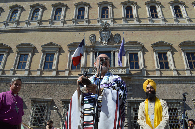 "Rabbi Lawrence Troster, from New Jersey, addresses marchers outside the French embassy in central Rome (Piazza Farnese) during a ""Many Faiths - One Planet"" march to the Vatican on June 28, 2015. Religion News Service photo by Rosie Scammell"