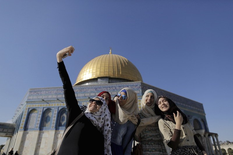 Palestinian Sanaa Abu Jaudi (L), 16, from the West Bank city of Jenin, takes a selfie photo with friends in front of the Dome of the Rock during the holy month of Ramadan, June 29, 2015