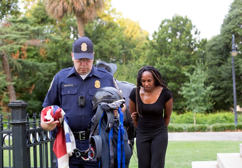 Bree Newsome walks behind a police officer after her arrest.
