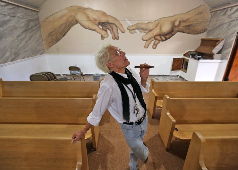 """Bill Levin poses in the sanctuary at The First Church of Cannabis, Tuesday, June 23, 2015. The sanctuary, still under renovation, includes a painting on the back wall of two hands passing a cannabis cigarette. The painting, by CS Stanley, the church's minister of art, is similar to a detail of the Michelangelo """"Creation of Adam"""" on the Sistine Chapel ceiling."""