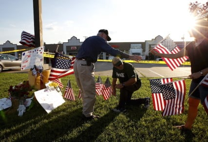 Mourners places flags at a growing memorial in front of the Armed Forces Career Center in Chattanooga, Tenn., July 16, 2015.