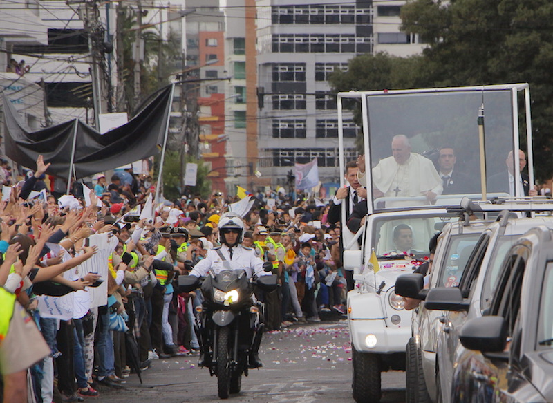 Pope Francis greets a crowd from the Popemobile in Quito, Ecuador.