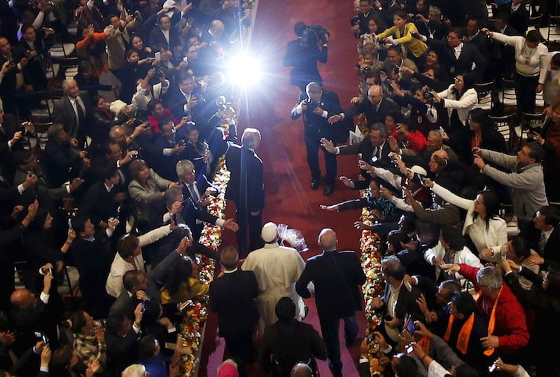 Pope Francis stands in an aisle with photographers snapping pictures.