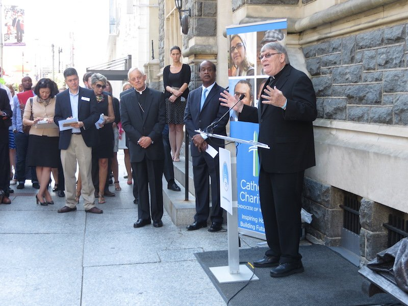 Catholic Charities President and CEO Rev. Msgr. John Enzler speaks at the Walk with Francis Pledge Launch (July 22) in front of the Catholic Charities Headquarters.