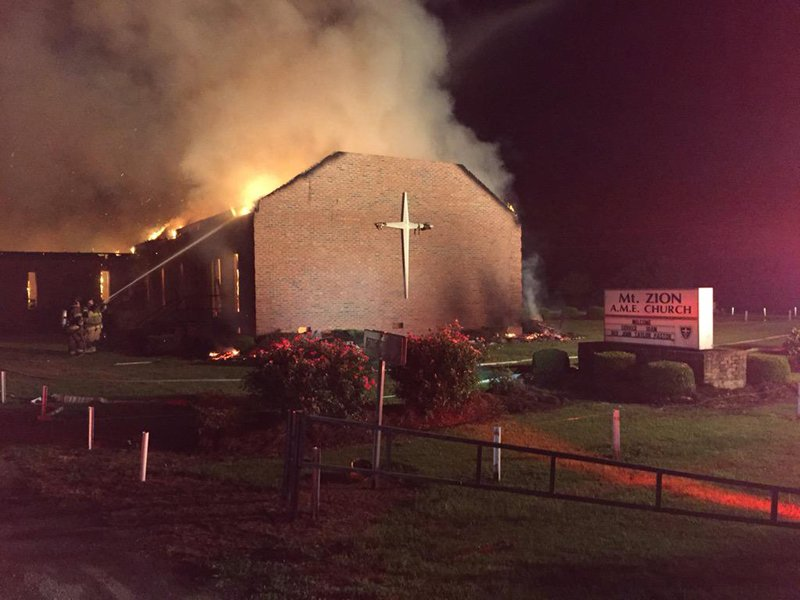 Fire crews try to control a blaze at the Mt. Zion African Methodist Episcopal Church in Greeleyville, South Carolina in this June 30, 2015 handout photo. The African-American church, which was burned down by the Ku Klux Klan 20 years ago, was the scene of another blaze on Tuesday, officials said, though the cause was not immediately clear. The fire comes amid a rash of fires that have erupted at black churches across the U.S. south, at least two of which have already been declared as deliberate. Photo courtesy of REUTERS/Clarendon County Fire Department/Handout via Reuters  *Editors: This photo may only be republished with RNS-CHURCH-FIRES, originally transmitted on July 1, 2015.