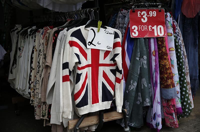 Pricing signs hang on clothing outside a shop in London, Britain on June 3, 2015. Photo courtesy of REUTERS/Suzanne Plunkett *Editors: This photo may only be republished with RNS-ENGLAND-SUNDAY, originally transmitted on July 7, 2015.