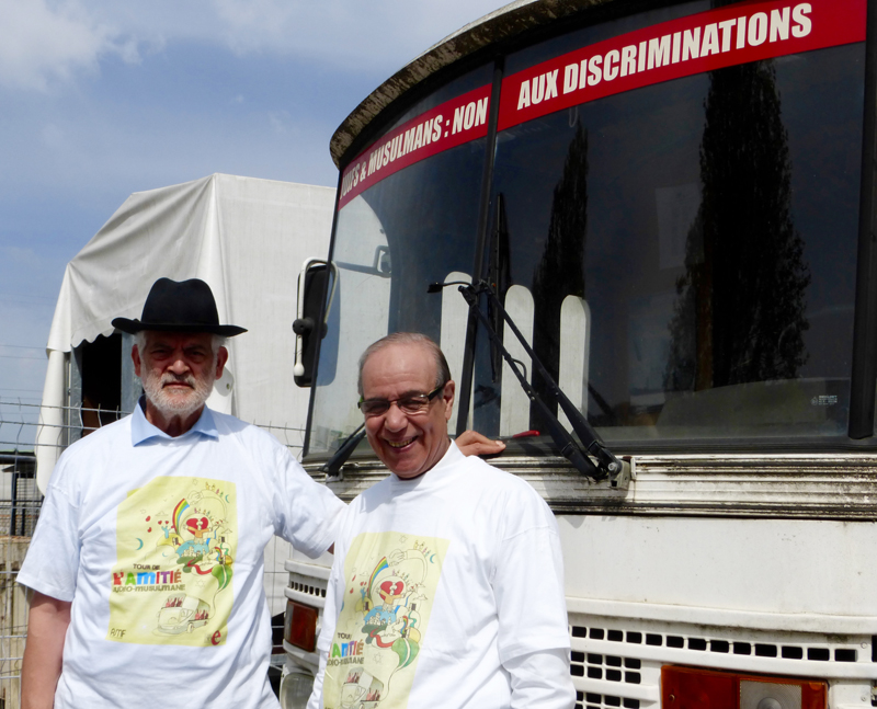 Rabbi Michel Serfaty and Imam Mohammed Azizi stand in front of Serfaty's bus. Religion News Service photo by Elizabeth Bryant