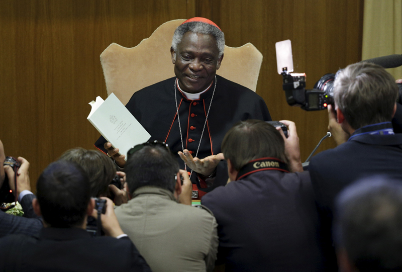 """Cardinal Peter Turkson poses as he holds Pope Francis's new encyclical titled """"Laudato Si (Be Praised), On the Care of Our Common Home"""", during the presentation news conference at the Vatican on June 18, 2015. Photo courtesy of REUTERS/Max Rossi *Editors: This photo may only be republished with RNS-TURKSON-ENVIRONMENT, originally transmitted on July 6, 2015."""