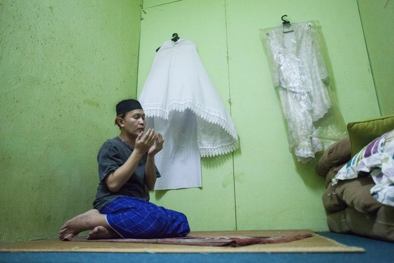 A transgender woman prays in a room adjacent to her beauty salon in Kuala Lumpur, Malaysia, on June 13, 2015. She prays in men's clothes, believing that in front of God she was born and always will be a man. She says she avoids going to mosques for fear of public shunning. Religion News Service photo by Alexandra Radu