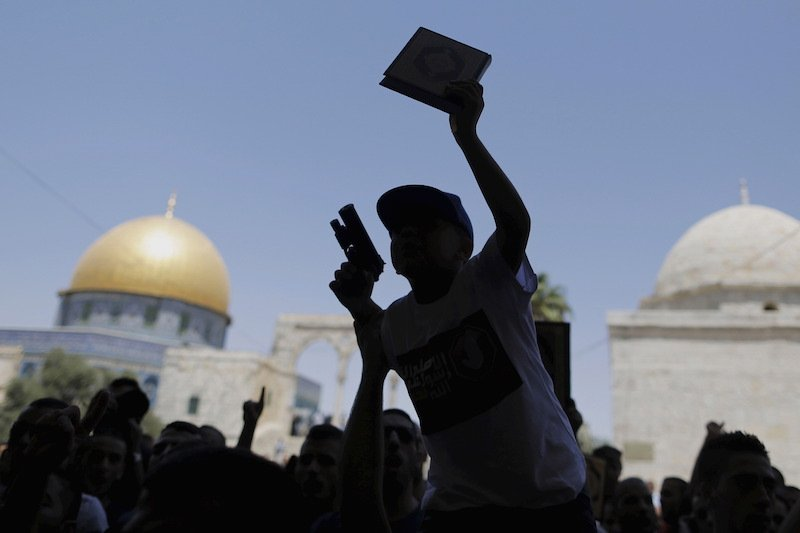 A Palestinian youth is silhouetted as he holds a toy gun and a Quran during a protest after Friday prayers on the compound known to Muslims as the Noble Sanctuary and to Jews as Temple Mount, in Jerusalem's Old City July 24, 2015. A few dozen Palestinians protested on Friday a day after an altercation between Jewish settlers and Palestinians took place at the compound. The Dome of the Rock is seen in the background.  Photo courtesy REUTERS/Ammar Awad.