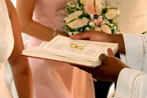 Wedding rings rest on a Bible during a ceremony.