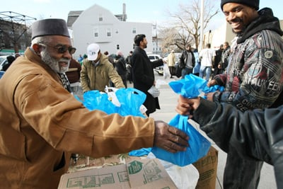 Musa Ajon Cherry, left, of Masjid Ashadul Yameen in East Orange, N.J., and volunteer Furquan Abdul, right, distribute bags of meat to people for the Islamic holiday of Eid al-Adha. Religion News Service photo by Mitsu Yasukawa /The Star Ledger.