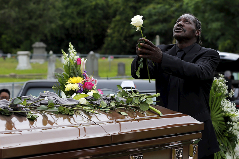 Gary Washington stands over the casket of his mother, Ethel Lance, as she is buried at the Emanuel African Methodist Episcopal Church cemetery in North Charleston, South Carolina on June 25, 2015. Lance is one of the nine victims of the mass shooting at the Emanuel African Methodist Episcopal Church. Photo courtesy of REUTERS/Brian Snyder *Editors: This photo may only be republished with RNS-BLACK-LIVES, originally transmitted on August 7, 2015.