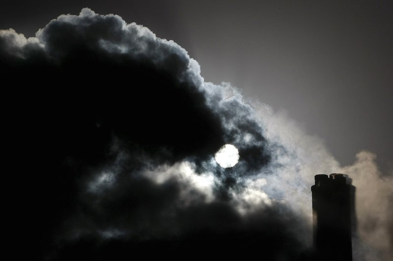 The sun is seen through the steam and other emissions coming from funnels of the brown coal power station in Australia. REUTERS/Mick Tsikas/Files
