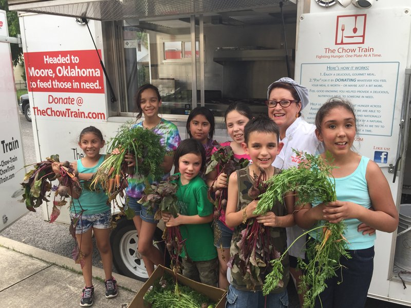 Joan Cheever poses with young farmers in front of The Chow Train food truck. Photo courtesy of The Chow Train